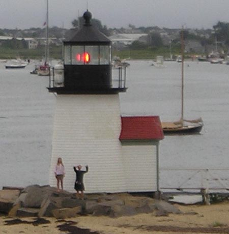 kids' silhouettes and a shining Brant Point Light